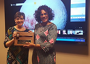President Dinelia Rosa (left) presents Past President Cathy McDaniels-Wilson with a leadership award.