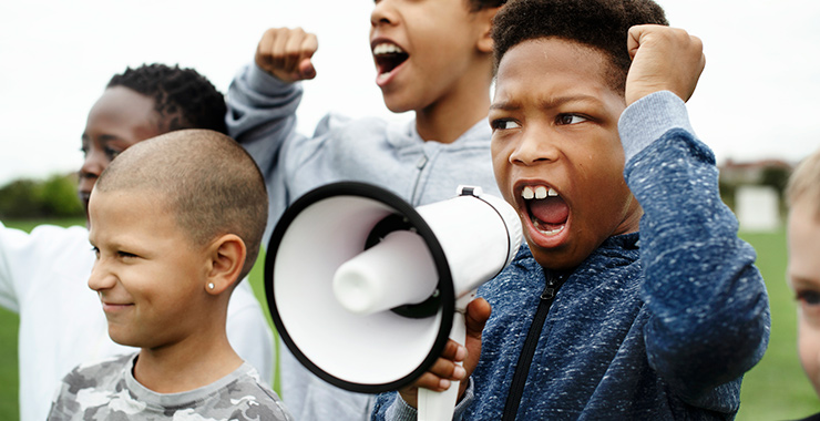Black boys yelling into a megaphone