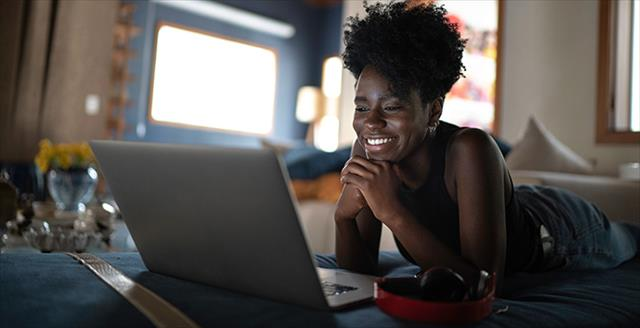 black woman smiling into computer